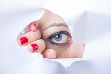 Een beeld van wman kijken door papier gat