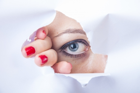 An image of wman looking through paper hole