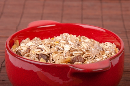 An image of hewalthy muesli in red ceramic bowl Stock Photo - 17607928
