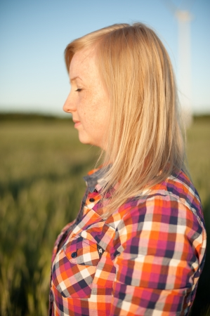 portrait of freckled blonde outside wearing a plaid shirt photo