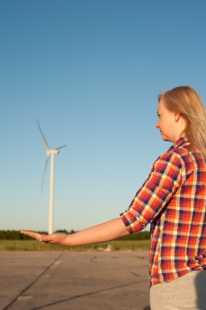An image of blonde girl and windturbine in the background photo