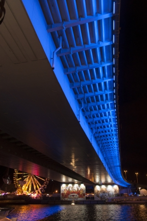 an image of bridge illuminated at night by the river