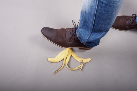 Businessman step into banana peel Stock Photo