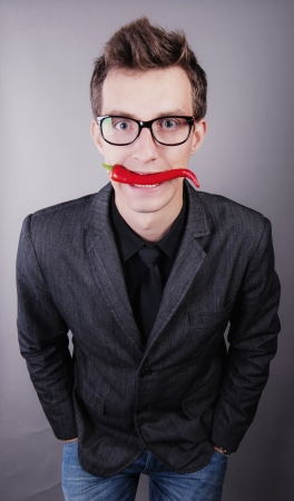an image of businessman with chili pepper in the mouth photo