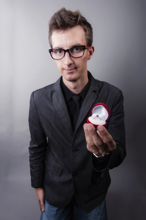 an image of man holding gold engagaement ring in red jewelery box photo