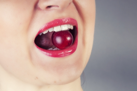 an image of girl eating cherry photo