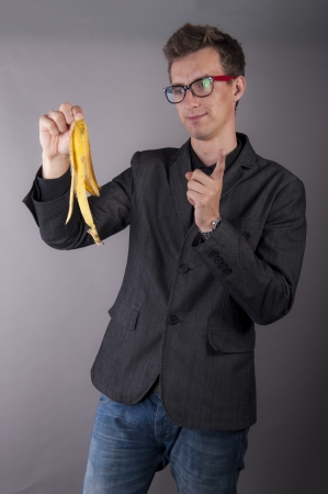 An image of young businessman holds a banana peel photo