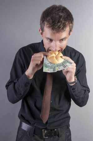an image of businessman is eating a sandwich with money photo