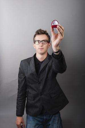 een beeld van de man die goud engagaement ring in rode juwelendoosje Stockfoto