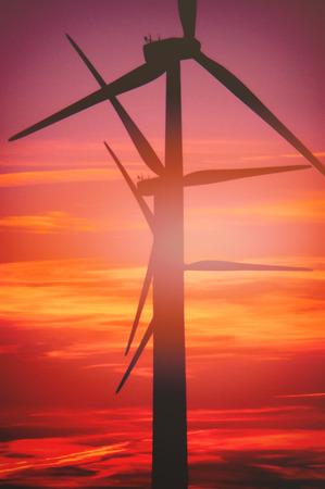 Windturbine boerderij met stralen van licht bij zonsondergang