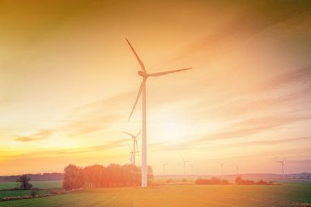 energías renovables: Granja de turbinas de viento con rayos de luz al atardecer  Foto de archivo