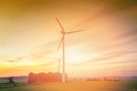 green energy resources: Wind turbine farm with rays of light at sunset Stock Photo