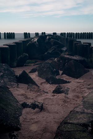 breakwaters: Breakwaters in the Baltic Sea at sunset Stock Photo