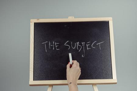subject: subject written in white chalk on a black chalkboard . gray background Stock Photo