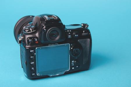 eos: Professional modern DSLR camera against blue background