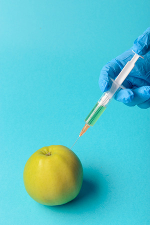 additives: Chemical additives in food or genetically modified fruit concept. Green apple with syringes of chemicals. Isolated on blue background. Stock Photo
