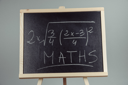 Math exercise written on the chalkboard. Gray background Stock Photo