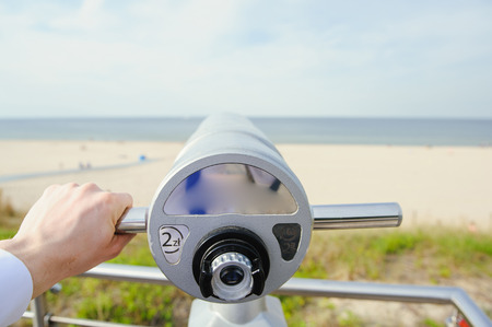 Close-Up of Sightseeing Binoculars with Beach Background Stock Photo