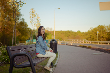 sits: The beautiful young city woman sits on a bench in the city Stock Photo
