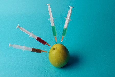 genetically: Chemical additives in food or genetically modified fruit concept. Green apple with syringes of chemicals. Isolated on blue background. Stock Photo