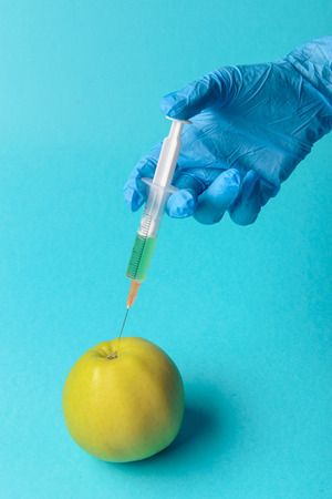 Chemical additives in food or genetically modified fruit concept. Green apple with syringes of chemicals. Isolated on blue background. Stock Photo