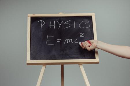 equivalence: Handwritten physics word and formula E=mc2 on chalkboard, gray background