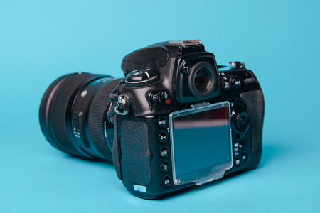 Professional modern DSLR camera against blue background