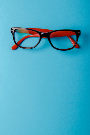 pair of red plastic-rimmed eyeglasses on a blue background