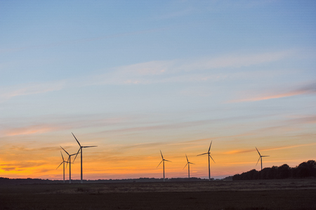 Silhouette of wind power station on sunset Stock Photo