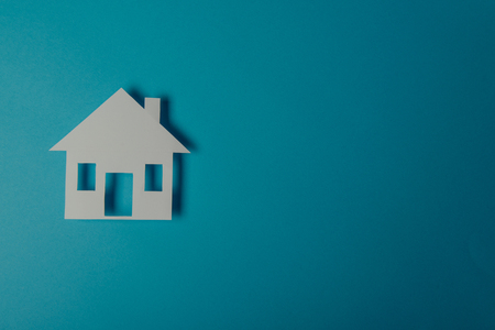paper cutout: House shaped paper cutout on on blue background Stock Photo