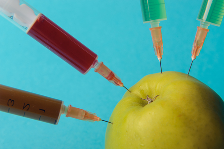 modified: Chemical additives in food or genetically modified fruit concept. Green apple with syringes of chemicals. Isolated on blue background. Stock Photo