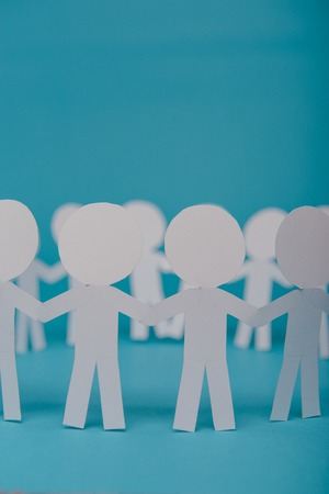 abstract paper people holding for hands on blue background 版權商用圖片