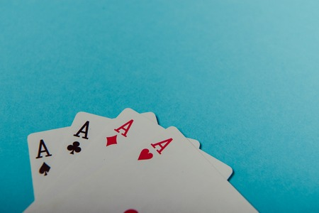A winning poker hand of four aces playing cards on blue background Stock Photo