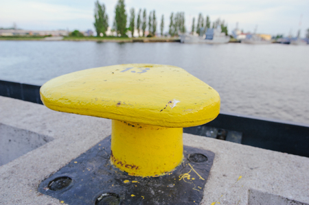 Horizontally oriented picture of port pier with yellow mooring bollard. Stock Photo