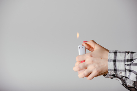 igniting: Hand with lighter igniting sparks on light background