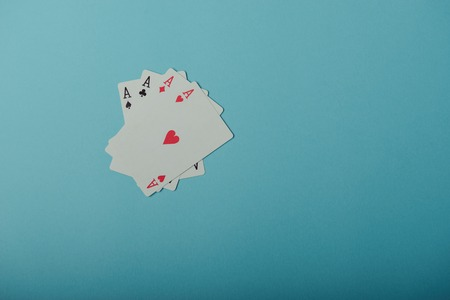 aces: A winning poker hand of four aces playing cards on blue background Stock Photo