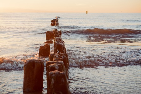 endlessly: Breakwaters in the Baltic sea over the sunset in summer