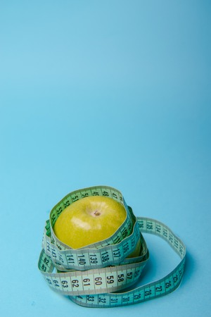 Green apple with measuring tape on blue background Stock Photo