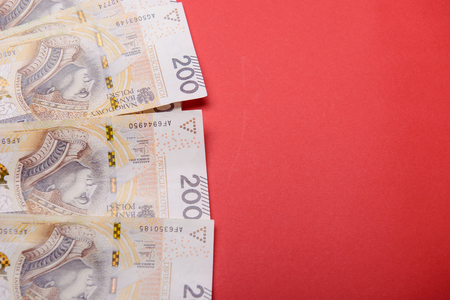 zloty: Polish zloty in notes and coins on red background
