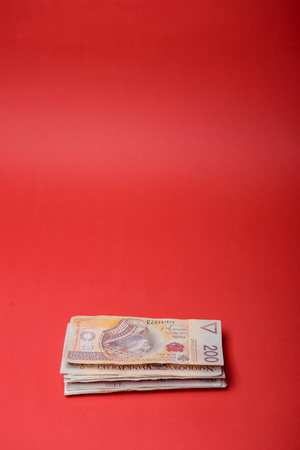 Polish zloty in notes and coins on red background