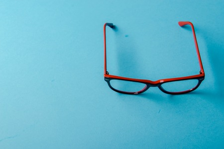 rimmed: pair of red plastic-rimmed eyeglasses on a blue background
