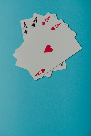 four objects: A winning poker hand of four aces playing cards on blue background Stock Photo