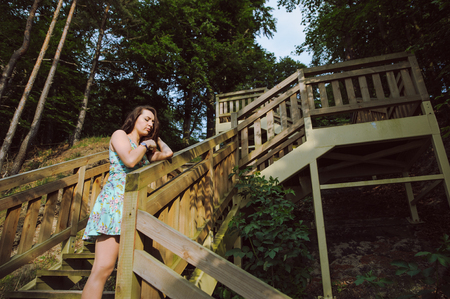 Brunette girl sitting on the wooden stairs in park and smiling photo