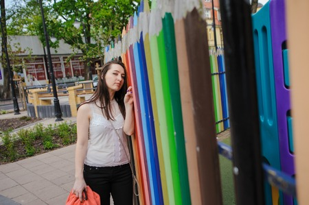 Young beautiful stylish girl standing against colourful pencils fence at city streets on a spring photo