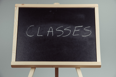 school bills: Classes written in white chalk on a black chalkboard . gray background