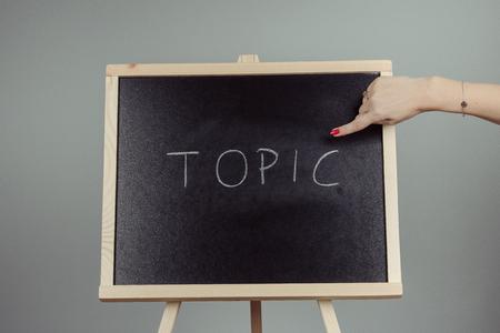 Topic written in white chalk on a black chalkboard . gray background