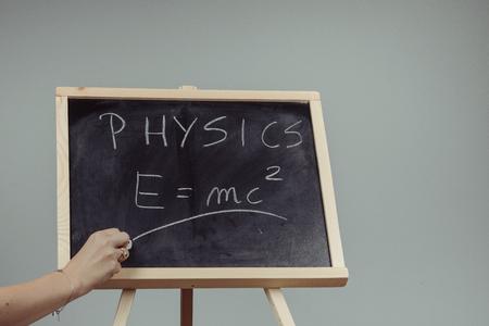 Handwritten physics word and formula E=mc2 on chalkboard, gray background