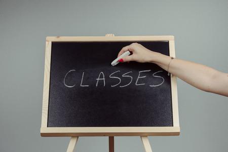 Classes written in white chalk on a black chalkboard . gray background