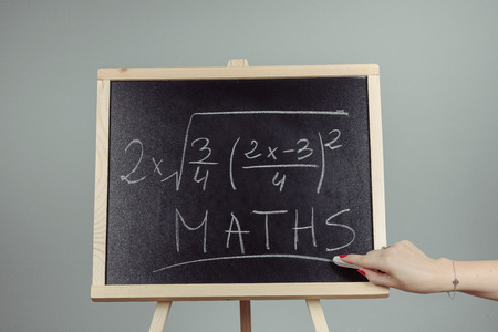 Math exercise written on the chalkboard. Gray background 写真素材