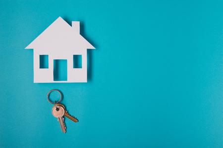 Srebrny klucz z postacią domu na niebieskim tle. Widok z góry.